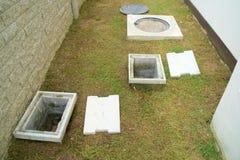 Ett manhålvatten och ett hål av fettfälla med avrinningsystemet runt om huset arkivbilder
