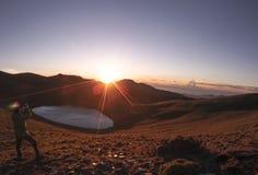 Ett manligt anseende på ett högre ställe, genom Jiaming sjön och att vänta på den härliga soluppgången Ordna till för att ta någr arkivfoto