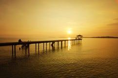 Ett mansammanträde på bron bara under solnedgång Arkivfoto