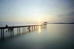 Ett mansammanträde på bron bara under solnedgång Royaltyfri Foto
