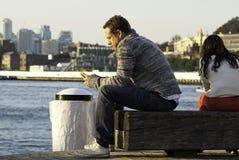 Ett mansammanträde på en brygga som ser hans telefon arkivfoton