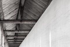 Ett massivt trätak i svartvitt stiger ovanför vit-stenen väggen royaltyfri bild