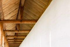 Ett massivt trätak stiger ovanför vit-stenen väggen royaltyfri fotografi