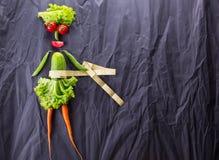 Ett matbegrepp av flickan med grönsaker på svart pappers- bakgrund Viktförlust och sund livsstil Med avstånd för text arkivbild