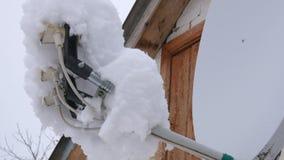 Ett maträtttorn på taket som täckas i snö Mycket snö på den satellit- maträtten lager videofilmer