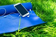 Ett mattt f?r yoga och pilates, en telefon med h?rlurar och p? gr?nt gr?s, royaltyfri foto