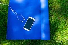 Ett mattt f?r yoga och pilates, en telefon med h?rlurar och p? gr?nt gr?s, royaltyfria foton