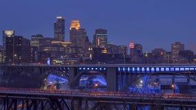 Ett medelskott av i stadens centrum Minneapolis och broar som spänner över Mississippiet River under en vinterskymning lager videofilmer