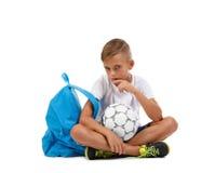 Ett meditativt pojkesammanträde på jordningen i lotusblommapositionen En unge med fotbollbollen som isoleras på en vit bakgrund Royaltyfri Foto