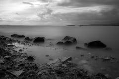 Ett minimalist långt exponeringsfoto av något stort vaggar i en sjö, w Arkivfoto