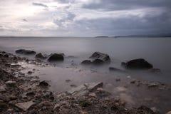 Ett minimalist långt exponeringsfoto av något stort vaggar i en sjö, w Arkivbild
