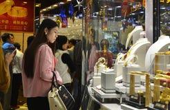 Ett modedamstopp som ser i fönstret av en guld, shoppar royaltyfri fotografi