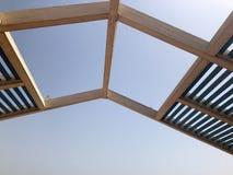 Ett modernt märkes- trendigt tak, en markis i det öppet med hål av strålar med bräden mot solen royaltyfria foton