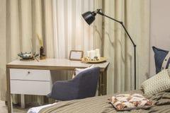 Ett modernt rum för en tonåring i den skandinaviska stilen - en säng, ett skrivbord, en fåtölj, gardiner, ett modernt sovrum och  arkivfoton