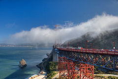 Ett moln som korsar Golden gate bridge i San Francisco Arkivbilder