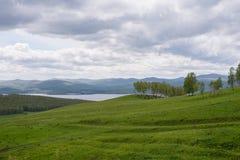 Ett molnigt vårlandskap med en blommande kulle och en sjö i avståndet royaltyfri fotografi