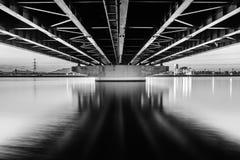 Ett monokromt landskap under en bro som bildar linjen modeller Denna bro förbinder den Mizumaki staden till den Ashiya staden i F royaltyfria bilder