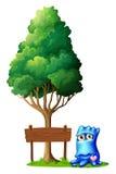 Ett monster bredvid den tomma skylten under trädet Arkivbild