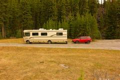 Ett motoriskt hem som bogserar en bil till och med alberta i våren royaltyfri foto