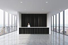 Ett mottagandeområde i ett modernt ljust rent kontor med en härlig receptionist i formell kläder Enorma panorama- fönster med nyt Royaltyfri Fotografi
