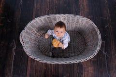 Ett mycket litet barn äter en torr bulle i en korg som vävas från ett vide- träd fotografering för bildbyråer