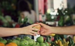 Ett mycket rött och grönt äpple passeras på en marknad Arkivbild