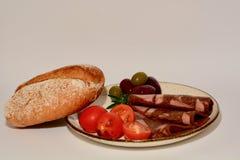 Ett närbildfoto av hurtigt mål eller mellanmålet som består av något kött, släntrar skivor, tomater, oliv och en bulle av rågbröd arkivbilder
