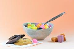 Ett närbildfoto av ett mål som består av några färgrika gelébönor, blandade sötsaker och kakor Begreppet av sjukligt bantar arkivfoto