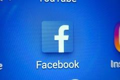 Ett närbildfoto av skärmen för Apple iPhonestart med symbolen för 'Facebook`-apps Royaltyfri Foto