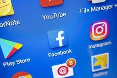 Ett närbildfoto av skärmen för Apple iPhonestart med symbolen för 'Facebook`-apps Royaltyfri Fotografi
