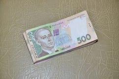 Ett närbildfotografi av en uppsättning av ukrainska pengar med ett nominellt värde av hryvnia som 500 ligger på en brun läderytte Royaltyfri Foto