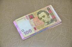 Ett närbildfotografi av en uppsättning av ukrainska pengar med ett nominellt värde av hryvnia som 100 ligger på en brun läderytte Royaltyfri Foto