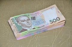 Ett närbildfotografi av en uppsättning av ukrainska pengar med ett nominellt värde av hryvnia som 500 ligger på en brun läderytte Royaltyfria Bilder