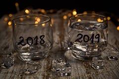 Ett nästan tomt exponeringsglas av året 2018 och ett annat fullt av det nya året 2019 arkivfoton