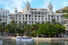 Ett nöjefartyg förbigår några historiska byggnader i Alicante Arkivbilder
