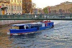 Ett nöjefartyg med turister seglar under Pochtamtsky bridg Arkivfoton