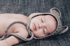 Ett nyfött behandla som ett barn i sömnar för ett lock på en grå pläd Royaltyfria Foton