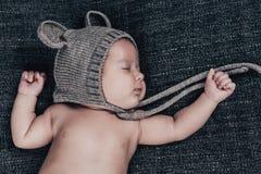 Ett nyfött behandla som ett barn i sömnar för ett lock på en grå pläd Arkivfoto