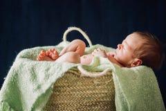 Ett nyfött behandla som ett barn pojken som sover i korgen arkivfoto