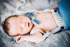 Ett nyfött behandla som ett barn pojken som sover i stucken fluga och byxa arkivbild
