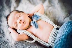 Ett nyfött behandla som ett barn pojken som sover i stucken fluga och byxa royaltyfria bilder