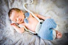 Ett nyfött behandla som ett barn pojken som sover i stucken fluga och byxa fotografering för bildbyråer