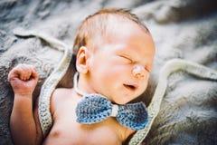 Ett nyfött behandla som ett barn pojken som sover i stucken fluga och byxa royaltyfri bild