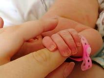 Ett nyfött behandla som ett barn rymmer moderfingret close upp arkivbilder