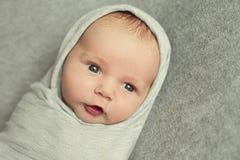 Ett nyfött behandla som ett barn är 9 gammalt för dagar som slås in i en grå torkduk som en Russ royaltyfri bild