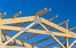 Ett nytt byggandetak med en träbråckbandram med en bakgrund för blå himmel arkivfoto