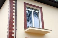 Ett nytt fönster i ett nytt hus Oavslutad balkong dekorativ murbruk dekorativa tegelplattor Det stads- huset eller byggnad, facad Royaltyfria Bilder