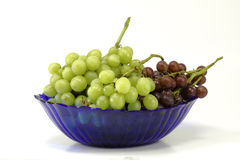 Gröna och purpurfärgade druvor i en blått bowlar Fotografering för Bildbyråer