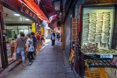 Ett oidentifierat folk shoppar på marknadsgatan Arkivbild
