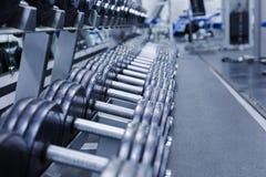 Ett område av hantlar på ställningen i idrottshallen i blått isolerade hantlar metal white arkivfoto